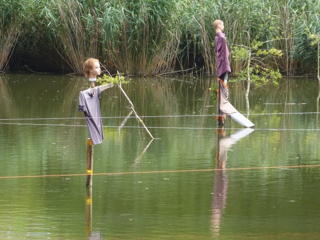 Etang dédié à la pisciculture avec de drôles d'épouvantails!